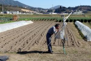 ライ麦を撒いた野菜畑の前で気象観測装置のデータをダウンロード