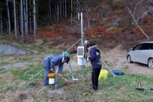 瓦礫をかき分けて気象観測装置,雨量計のケーブルを地中に埋設します.